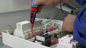 Τα χέρια του εργαζομένου ελέγχουν το δείκτη τάσης επαφών στην ηλεκτρονική στο εργοστάσιο φιλμ μικρού μήκους