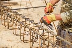 Τα χέρια του εργαζομένου στα προστατευτικά γάντια πλέκουν τις ράβδους μετάλλων με το καλώδιο στοκ εικόνες