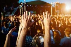 Τα χέρια του ευτυχούς πλήθους ανθρώπων που έχει τη διασκέδαση στο καλοκαίρι ζουν φεστιβάλ βράχου Στοκ εικόνες με δικαίωμα ελεύθερης χρήσης