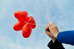 Τα χέρια του ζεύγους κρατούν ballons σε μια κόκκινη καρδιά Στοκ φωτογραφίες με δικαίωμα ελεύθερης χρήσης