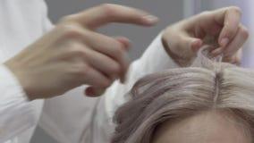 Τα χέρια του κομμωτή δίνουν έμφαση στα σκέλη της τρίχας φιλμ μικρού μήκους