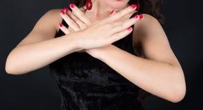 Τα χέρια του κοριτσιού που διασχίζονται symmetrically στο στήθος με κόκκινο nai Στοκ Φωτογραφίες