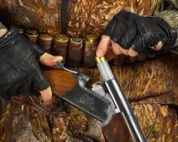Τα χέρια του κυνηγού φορτώνουν το κυνηγετικό όπλο για το πυροβολισμό στοκ εικόνες