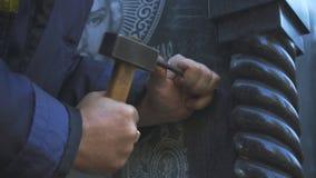 Τα χέρια του κυρίου επιλέγουν μια χάραξη στην πέτρα φιλμ μικρού μήκους