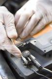 Τα χέρια του μηχανικού αυτοκινήτων στα μίας χρήσης γάντια ξεβιδώνουν το συμπλέκτη μπαταριών Στοκ εικόνες με δικαίωμα ελεύθερης χρήσης