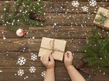Τα χέρια του παιδιού ανοίγουν ένα δώρο Στοκ Εικόνα