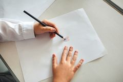 Τα χέρια του παιδιού είναι χρωματισμένα με τα χρωματισμένα μολύβια σε ένα άσπρο φύλλο του εγγράφου για έναν ξύλινο πίνακα στοκ εικόνα με δικαίωμα ελεύθερης χρήσης