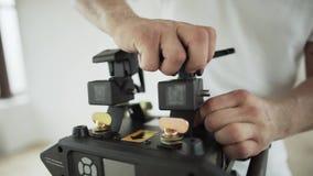 Τα χέρια του τύπου θέτουν τα διαφορετικά πράγματα στη μαύρη πλαστική συσκευή στο δωμάτιο απόθεμα βίντεο