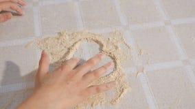 Τα χέρια του Chld χρωματίζουν μια καρδιά από το αλεύρι στον πίνακα κουζινών φιλμ μικρού μήκους