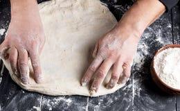 Τα χέρια των ατόμων ζυμώνουν ένα στρογγυλό κομμάτι της ζύμης στοκ εικόνες με δικαίωμα ελεύθερης χρήσης