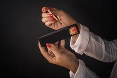 Τα χέρια των γυναικών αναφλέγουν τις μεγάλες αντιστοιχίες για ένα tompus cigare ή ένα firepla Στοκ φωτογραφία με δικαίωμα ελεύθερης χρήσης