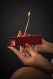 Τα χέρια των γυναικών αναφλέγουν τις μεγάλες αντιστοιχίες για ένα tompus cigare ή ένα firepla Στοκ εικόνα με δικαίωμα ελεύθερης χρήσης