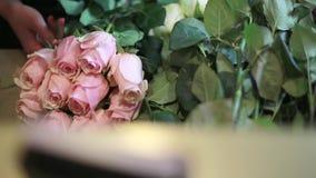 Τα χέρια των γυναικών είναι παίρνουν τα ρόδινα τριαντάφυλλα στο storefront απόθεμα βίντεο