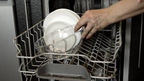Τα χέρια των γυναικών παίρνουν έξω τα καθαρά πιάτα από το πλυντήριο πιάτων, που παρουσιάζει καθαρά μαχαιροπήρουνα Εγχώριες συσκευ απόθεμα βίντεο