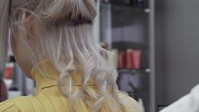 Τα χέρια των κομμωτών γυναικών κάνουν τις ογκομετρικές μπούκλες απόθεμα βίντεο