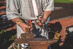Τα χέρια των μερών σιδηρουργών σφυρηλατημένων κομματιών μετάλλων στο παλαιό αμόνι πέρα από ανοίγουν πυρ Λαϊκή τέχνη Στοκ εικόνες με δικαίωμα ελεύθερης χρήσης