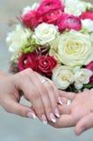 Τα χέρια των νέων παντρεμένων ζευγαριών και της γαμήλιας ανθοδέσμης Στοκ Εικόνες