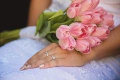 Τα χέρια των παντρεμένων ζευγαριών και της γαμήλιας ανθοδέσμης Στοκ Εικόνες