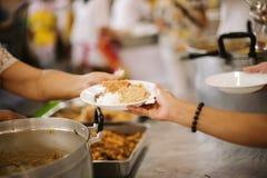 Τα χέρια των προσφύγων έχουν βοηθηθεί από τα τρόφιμα φιλανθρωπίας για να ανακουφίσουν την πείνα: η έννοια του ανθρωπισμού στοκ φωτογραφίες με δικαίωμα ελεύθερης χρήσης
