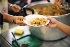 Τα χέρια των προσφύγων έχουν βοηθηθεί από τα τρόφιμα φιλανθρωπίας για να ανακουφίσουν την πείνα: η έννοια του ανθρωπισμού στοκ εικόνα με δικαίωμα ελεύθερης χρήσης