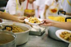 Τα χέρια των φτωχών περιμένουν τις δωρεές τροφίμων να ανακουφίσουν την πείνα: έννοια της σίτισης στοκ φωτογραφία