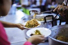 Τα χέρια των φτωχών περιμένουν τις δωρεές τροφίμων να ανακουφίσουν την πείνα: έννοια της σίτισης στοκ φωτογραφίες