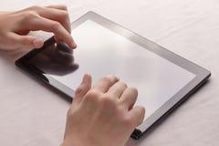 Τα χέρια χρησιμοποιούν μια μαύρη ταμπλέτα σε ένα άσπρο σεντόνι στοκ εικόνες με δικαίωμα ελεύθερης χρήσης