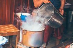 Τα χέρια χύνουν το νερό στο δοχείο για βράζουν Βράστε το νερό για τα τρόφιμα στοκ εικόνες