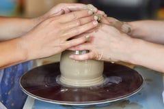 Τα χέρια δύο ανθρώπων δημιουργούν το δοχείο, ρόδα αγγειοπλαστών ` s Αγγειοπλαστική διδασκαλίας Στοκ φωτογραφία με δικαίωμα ελεύθερης χρήσης