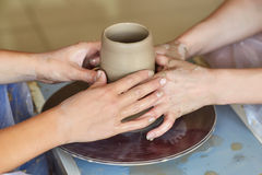 Τα χέρια δύο ανθρώπων δημιουργούν το δοχείο, ρόδα αγγειοπλαστών ` s Αγγειοπλαστική διδασκαλίας Στοκ εικόνες με δικαίωμα ελεύθερης χρήσης