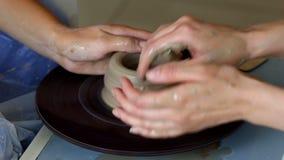 Τα χέρια δύο ανθρώπων δημιουργούν το δοχείο, ρόδα αγγειοπλαστών ` s Αγγειοπλαστική διδασκαλίας φιλμ μικρού μήκους