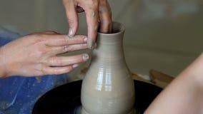 Τα χέρια δύο ανθρώπων δημιουργούν το δοχείο, ρόδα αγγειοπλαστών ` s Αγγειοπλαστική διδασκαλίας απόθεμα βίντεο
