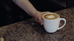Τα χέρια Barista δίνουν ένα φλυτζάνι του cappuccino Νεαρός άνδρας απόθεμα βίντεο