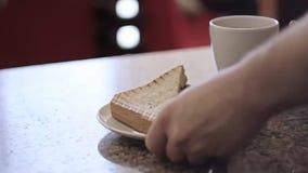 Τα χέρια Barista δίνουν το σάντουιτς δύο και ένα φλυτζάνι καυτού απόθεμα βίντεο