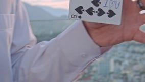 Τα χέρια Conjurer κινηματογραφήσεων σε πρώτο πλάνο αναποδογυρίζουν την κάρτα με τη σημείωση στο τέχνασμα φιλμ μικρού μήκους