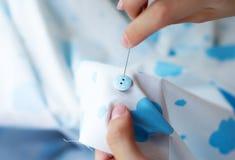 Τα χέρια seamstress ράβουν ένα κουμπί με μια βελόνα Στοκ Φωτογραφία