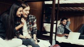 Τα χαμογελώντας κορίτσια κάθονται στο κρεβάτι και εξέταση τον τύπο στοκ φωτογραφίες με δικαίωμα ελεύθερης χρήσης
