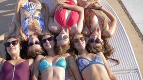 Τα χαμογελώντας κορίτσια φίλων ομάδας στα κοστούμια λουσίματος και τα γυαλιά βρίσκονται κάτω από τον ήλιο στο μόνιππο longue στις φιλμ μικρού μήκους