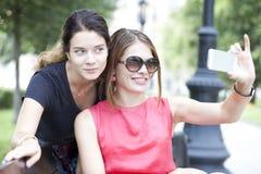 Τα χαμογελώντας νέα κορίτσια με το κύτταρο τηλεφωνούν στη συνεδρίαση σε έναν πάγκο σε ένα πάρκο Στοκ Φωτογραφία