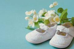 Τα χαριτωμένα, άσπρα εκλεκτής ποιότητας παπούτσια μωρών νηπίων δέρματος με την άνοιξη ανθίζουν στο κυανό υπόβαθρο και το δωμάτιο  Στοκ Εικόνες