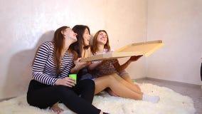 Τα χαριτωμένα κορίτσια δροσερά ξοδεύουν το χρόνο και απολαμβάνουν την πίτσα, κάθονται στο πάτωμα στη φωτεινή κρεβατοκάμαρα το βρά απόθεμα βίντεο
