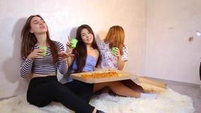 Τα χαριτωμένα κορίτσια δροσερά ξοδεύουν το χρόνο και απολαμβάνουν την πίτσα, κάθονται στο πάτωμα στη φωτεινή κρεβατοκάμαρα το βρά φιλμ μικρού μήκους