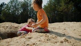 Τα χαριτωμένα κορίτσια παίζουν στην άμμο στα ξύλα απόθεμα βίντεο