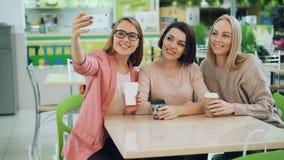 Τα χαριτωμένα κορίτσια παίρνουν selfie με τη συνεδρίαση smartphone στον πίνακα στον άνετο καφέ και θέτουν με τον καφέ Φιλία, ευχά απόθεμα βίντεο