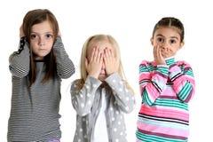 Τα χαριτωμένα κορίτσια που ενεργούν έξω ακούνε ότι μην δείτε και μιλήστε κανένα κακό στοκ εικόνες
