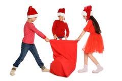 Τα χαριτωμένα παιδιά στα καπέλα Santa με τα κόκκινα Χριστούγεννα τοποθετούν σε σάκκο στο άσπρο υπόβαθρο Στοκ Εικόνα
