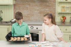 Τα χαριτωμένα παιδιά έψησαν τα μπισκότα και δοκιμή του στον πίνακα στην εγχώρια κουζίνα Στοκ Φωτογραφία