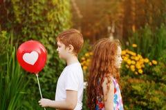 Τα χαριτωμένα παιδιά κρατούν τα κόκκινα μπαλόνια με την καρδιά στο θερινό πάρκο Στοκ Εικόνες