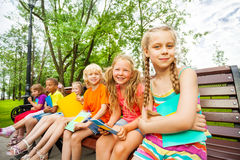 Τα χαριτωμένα παιδιά με τα σημειωματάρια κάθονται στον πάγκο Στοκ εικόνα με δικαίωμα ελεύθερης χρήσης