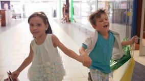 Τα χαρούμενα παιδιά με τις τσάντες αγορών τρέχουν για να κάνουν τις αγορές στις εκπτώσεις κατά τη διάρκεια των πωλήσεων τη μαύρη  απόθεμα βίντεο
